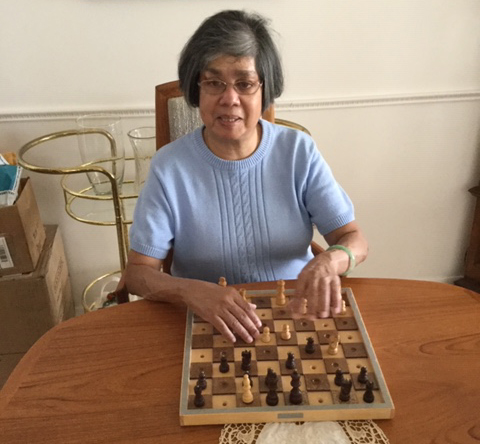A photograph of Donna in a blue sweater, seated at a table with an adaptive chess board in front of her.