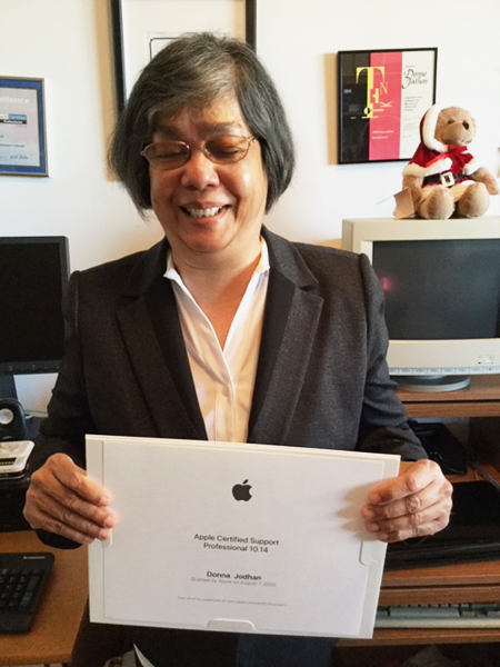Donna holding her Apple-Certified Support Professional certificate and smiling.