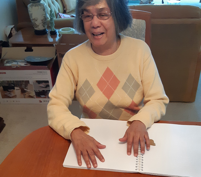 A photo of Donna reading her chess book printed in Braille.