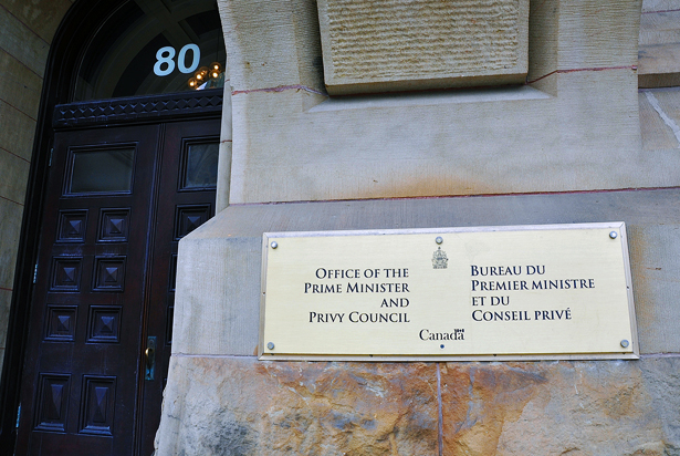 A photo of the sign for the Office of the Prime Minister and Privy Council on a stone wall at 80 Wellington Street in Ottawa, Canada.