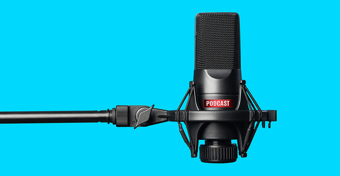 A black podcast microphone in front of a blue background.