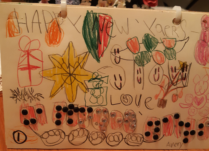 Another inside page, featuring resents, stars, happy faces, dog paw prints, and many Christmas decorations. It says 'happy New Years' in Braille.